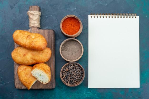 Draufsicht köstliche kuchen mit fleischfüllung und gewürzen auf dem dunkelblauen hintergrundteigkuchenbrötchen-backgebäck
