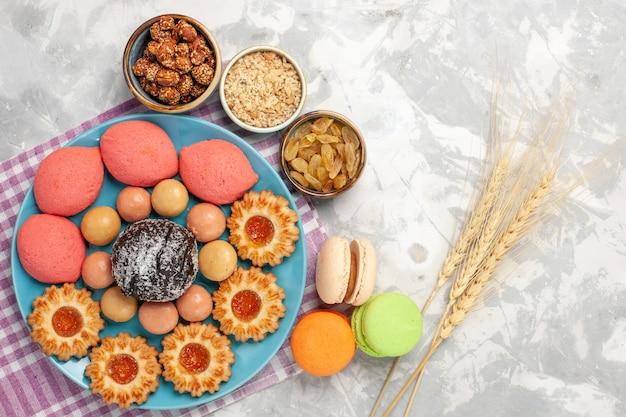 Draufsicht köstliche kuchen mit keksen und macarons auf weißer oberfläche