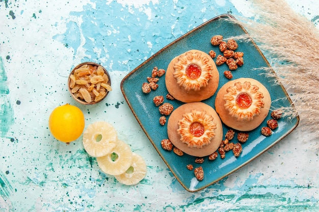 Draufsicht köstliche kuchen mit keksen und süßen nüssen auf hellblauem schreibtisch backen kekskuchen süße zuckernuss