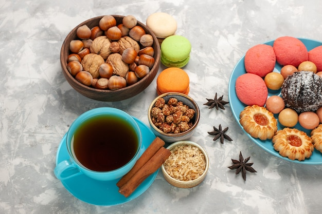 Draufsicht köstliche kuchen mit macarons nüssen tee und keksen auf der weißen oberfläche