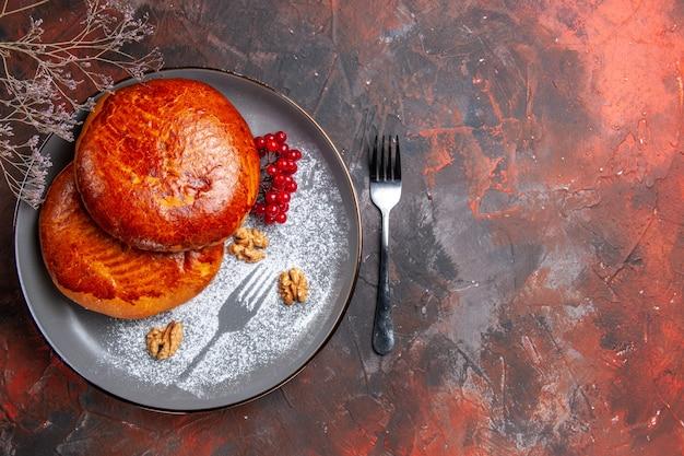 Draufsicht köstliche kuchen mit roten beeren auf dem dunklen tischkuchen süßer gebäckkuchen