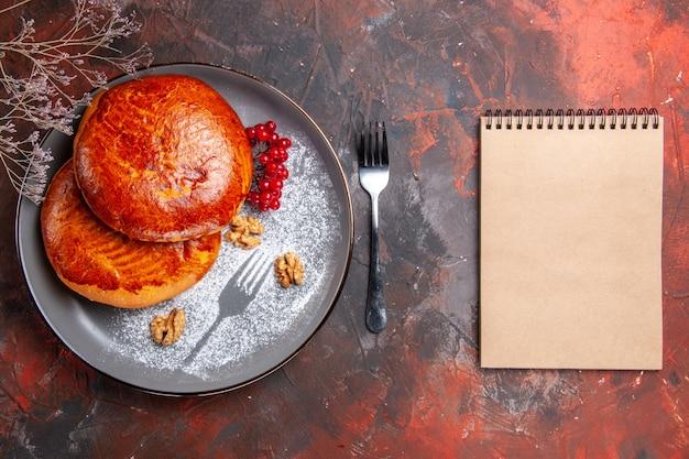 Draufsicht köstliche kuchen mit roten beeren auf dunklem gebäckkuchen des dunklen tischkuchens