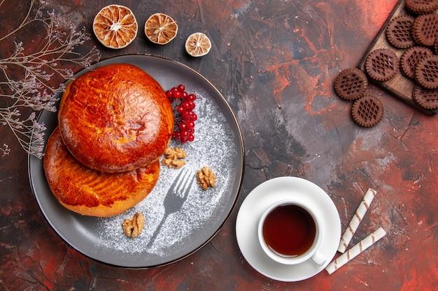 Draufsicht köstliche kuchen mit tasse tee auf dem dunklen tisch süßes kuchenkuchengebäck