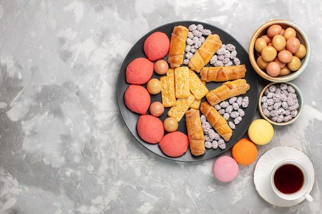 Draufsicht köstliche kuchen mit tasse tee bagels cracker und süßigkeiten auf hellweißem schreibtischkuchen kekskeks süßer zuckerkuchen