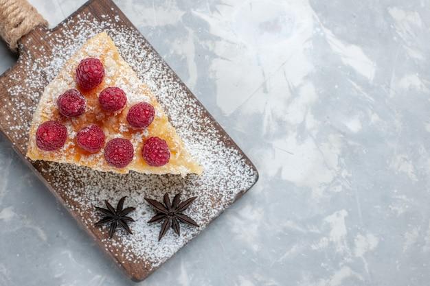 Draufsicht köstliche kuchenscheibe mit himbeeren auf leichtem schreibtischkuchenkeks süßer zuckerauflauf