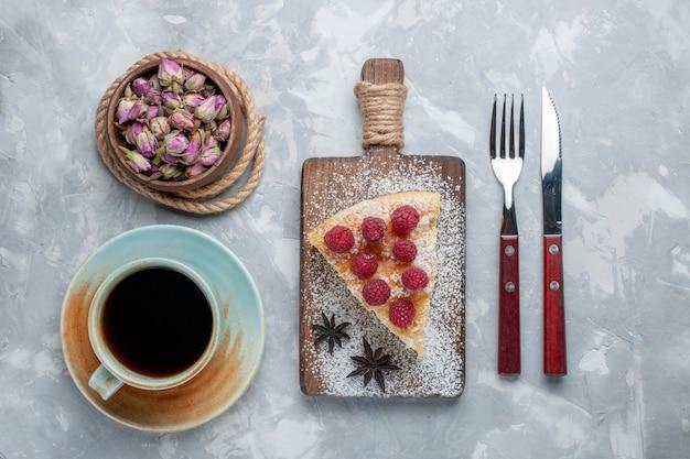 Draufsicht köstliche kuchenscheibe mit himbeeren und tee auf leichtem schreibtischkuchenkeks süßer zuckerauflauf