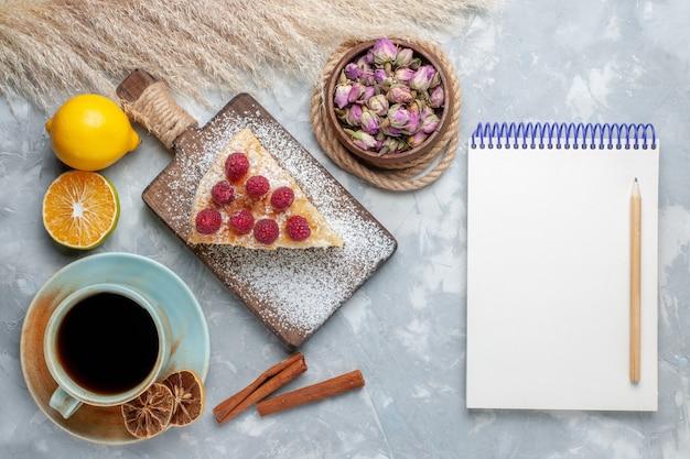 Draufsicht köstliche kuchenscheibe mit tasse tee und zitronenblock auf dem leichten schreibtischkuchenkeks süßer zuckerauflauf