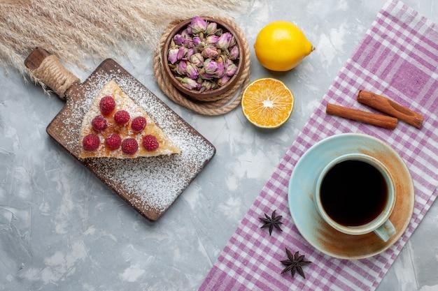 Draufsicht köstliche kuchenscheibe mit tasse tee und zitronenscheibe auf leichtem schreibtischkuchenkeks süßer zuckerauflauf