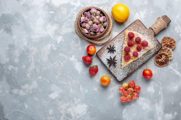 Draufsicht köstliche kuchenscheibe mit zitrone und früchten auf leichtem schreibtischkuchenkeks süßer zuckerauflauf