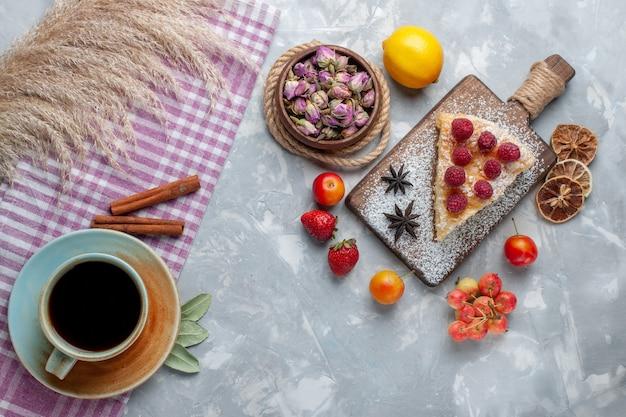 Draufsicht köstliche kuchenscheibe mit zitronentee und früchten auf leichtem schreibtischkuchenkeks süßem zucker backen