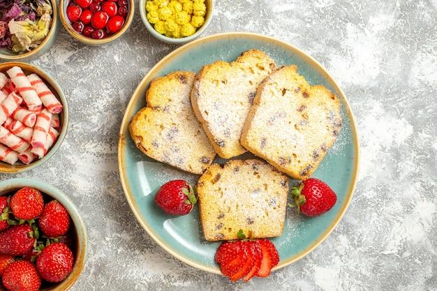 Draufsicht köstliche kuchenscheiben mit früchten und bonbons auf leichter oberfläche backt süße torte
