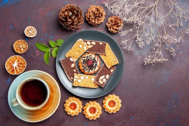 Draufsicht köstliche kuchenscheiben mit kleinem keks und tasse tee auf dem dunklen hintergrund keks-cookie-dessert-kuchen-tee süß