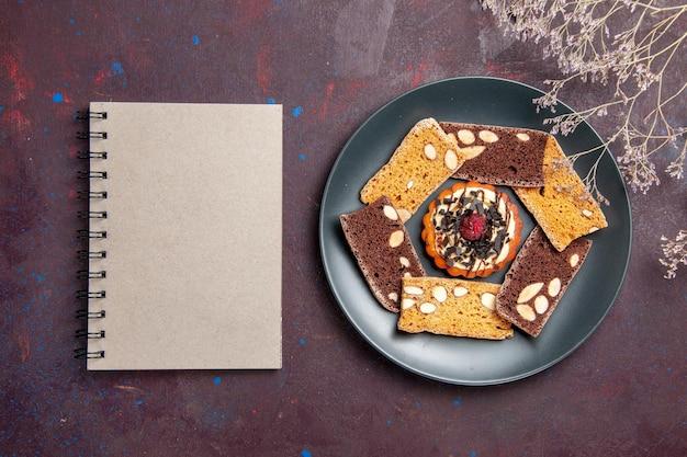 Draufsicht köstliche kuchenscheiben mit nüssen und kleinem keks auf dunklem hintergrund keks-cookie-dessert-kuchen-tee süß tea