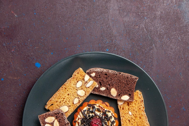 Draufsicht köstliche kuchenscheiben mit nüssen und kleinem keks auf dunklem hintergrund süßer keksplätzchen-dessertkuchen