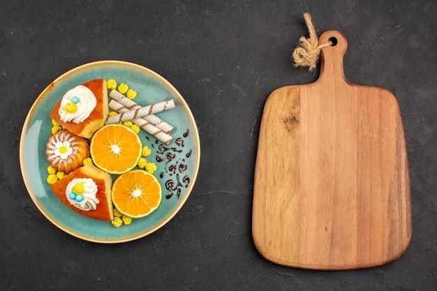 Draufsicht köstliche kuchenscheiben mit pfeifenkeksen und geschnittenen mandarinen auf dunklem hintergrund obstkuchenkuchenplätzchen süßer tee