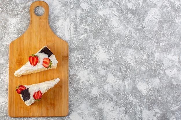 Draufsicht köstliche kuchenscheiben mit schokoladencreme und erdbeere auf dem hellen hintergrundkuchenkekszuckersüß