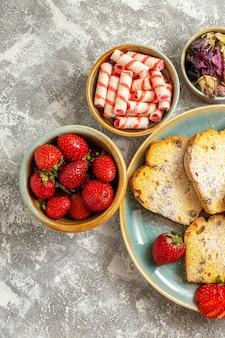 Draufsicht köstliche kuchenstücke mit früchten auf hellem obstkuchen süßer torte der leichten oberfläche