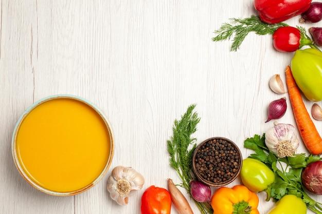 Draufsicht köstliche kürbissuppencreme mit gemüse auf weißem schreibtisch reife suppensaucenmahlzeit strukturiert