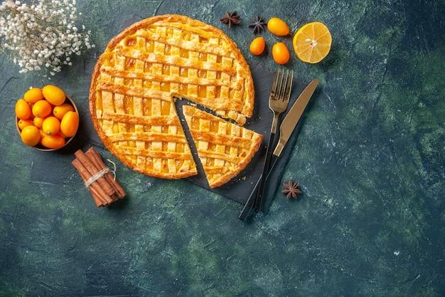 Draufsicht köstliche kumquat-torte mit geschnittenem stück auf dunklem hintergrund