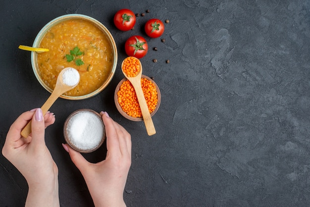 Draufsicht köstliche linsensuppe mit frau, deren salz in ihre suppe auf dunkler oberfläche gießt