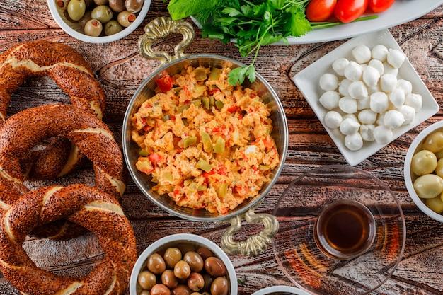 Draufsicht köstliche mahlzeit in teller mit türkischem bagel, einer tasse tee, salat, gurken auf holzoberfläche