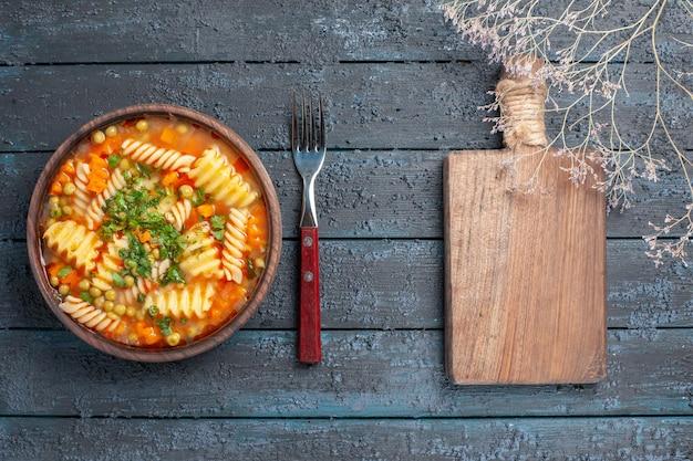 Draufsicht köstliche nudelsuppe aus italienischer spiralnudeln mit grüns auf dem dunklen rustikalen schreibtisch abendessen gericht italienische nudelsuppe soße