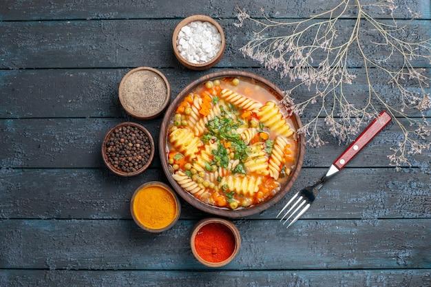 Draufsicht köstliche nudelsuppe mit gemüse und gewürzen auf dunkelblauem schreibtisch abendessen gericht italienische nudelsuppe