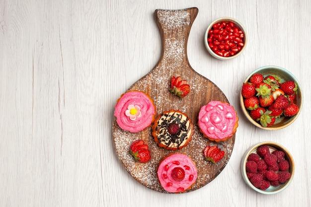 Draufsicht köstliche obstkuchen cremige desserts mit beeren und früchten auf weißem hintergrund sahnetee süßer keks dessertkuchen