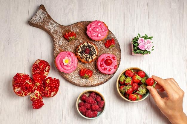 Draufsicht köstliche obstkuchen cremige desserts mit früchten und beeren auf weißem hintergrund sahnetee süßer kuchen cookie dessert