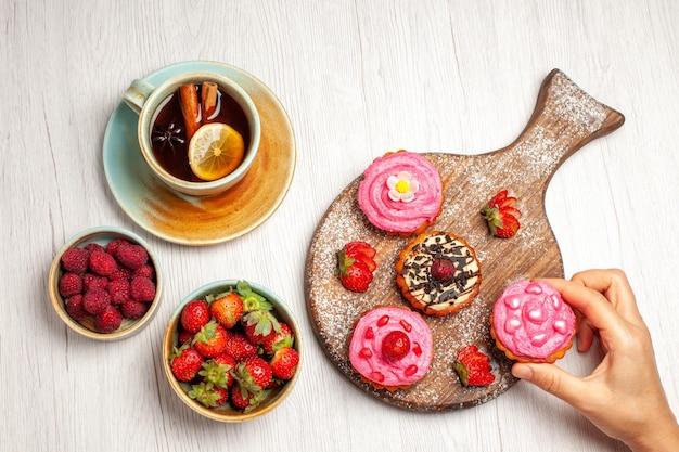 Draufsicht köstliche obstkuchen cremige desserts mit früchten und tasse tee auf weißem hintergrund sahnetee süßer dessertkuchen cookie