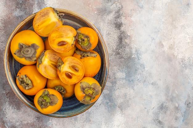 Draufsicht köstliche persimonen geschnittene persimonen in runder holzkiste auf nacktem hintergrund