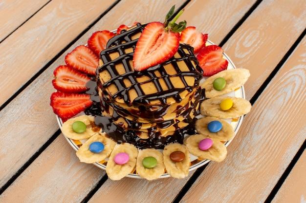 Draufsicht köstliche pfannkuchen innerhalb der weißen platte mit geschnittenen roten erdbeeren und bananen auf dem braunen hölzernen hintergrund