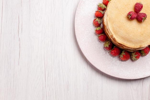 Draufsicht köstliche pfannkuchen mit frischen roten erdbeeren auf weißem hintergrund obstkuchen kuchen beerenkeks zucker süß