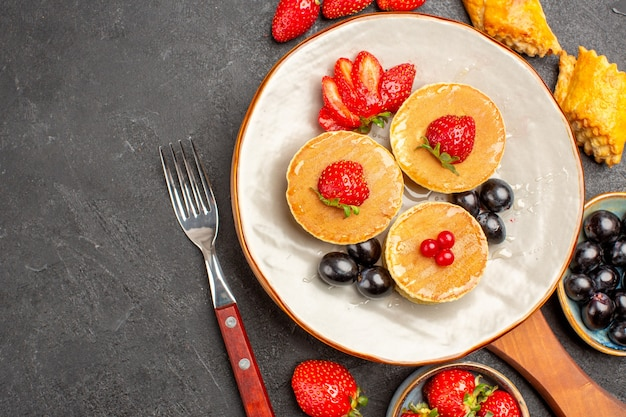 Draufsicht köstliche pfannkuchen mit früchten auf der dunklen oberfläche kuchenfruchtkuchen süß