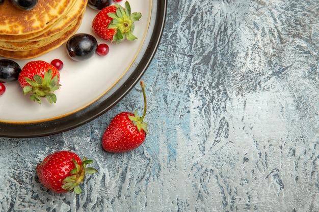 Draufsicht köstliche pfannkuchen mit früchten auf leichtem süßem obstkuchen der leichten oberfläche