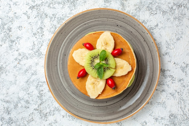Draufsicht köstliche pfannkuchen mit geschnittenen früchten im teller auf weißer oberfläche obst süße dessert zuckerkuchen frühstücksfarbe