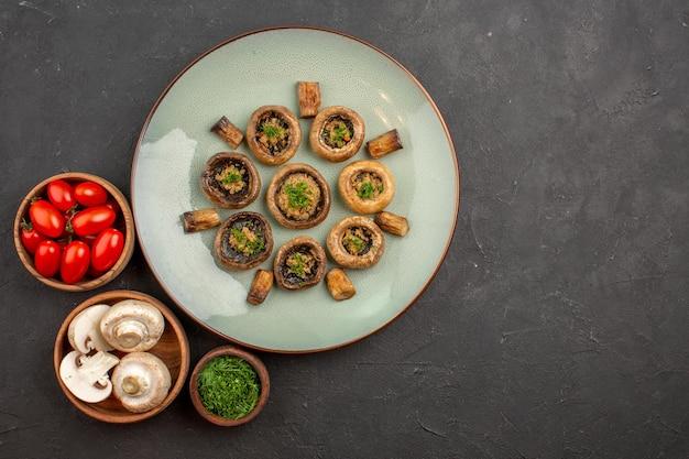 Draufsicht köstliche pilzmahlzeit mit frischem grün und tomaten auf dem dunklen oberflächengericht abendessenmahlzeit, das pilze kocht