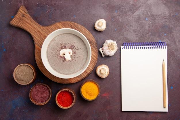 Draufsicht köstliche pilzsuppe mit gewürzen auf dunklem schreibtisch