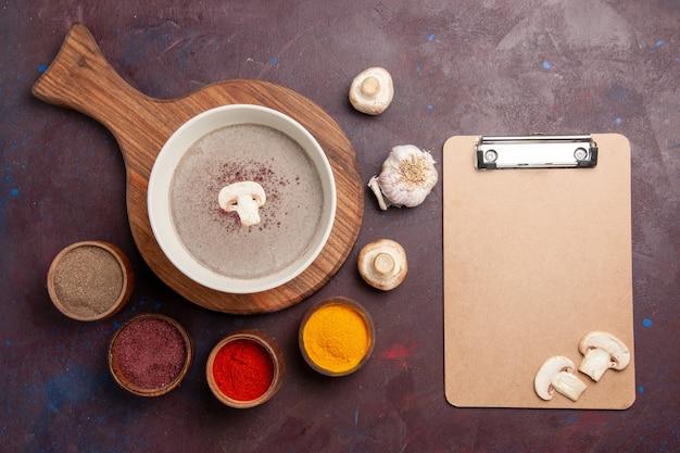 Draufsicht köstliche pilzsuppe mit verschiedenen gewürzen auf dunklem raum