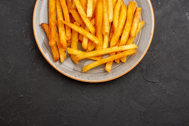 Draufsicht köstliche pommes frites im teller auf dunklem hintergrund kartoffeln burger mahlzeit sandwich abendessen gericht