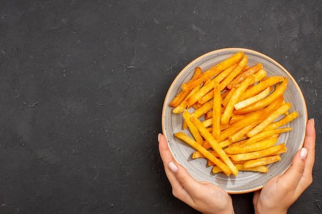 Draufsicht köstliche pommes frites im teller auf dunklem hintergrund kartoffeln mahlzeit sandwich gericht burger