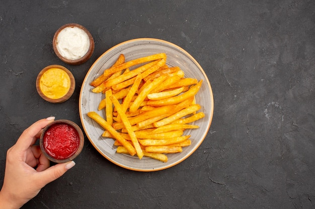 Draufsicht köstliche pommes frites mit gewürzen auf dunklem hintergrund kartoffelmahlzeit fast-food-gericht burger