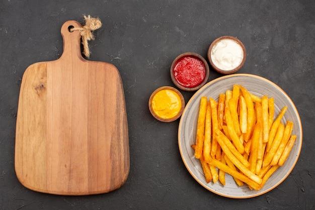 Draufsicht köstliche pommes frites mit gewürzen auf dunklem hintergrund mahlzeit kartoffeln fast-food-burger-gericht