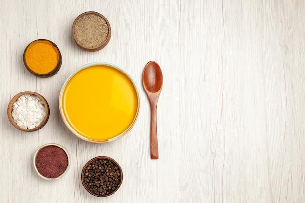 Draufsicht köstliche sahnesuppe mit verschiedenen gewürzen auf weißem holztisch suppensauce mahlzeit sahne abendessen gericht