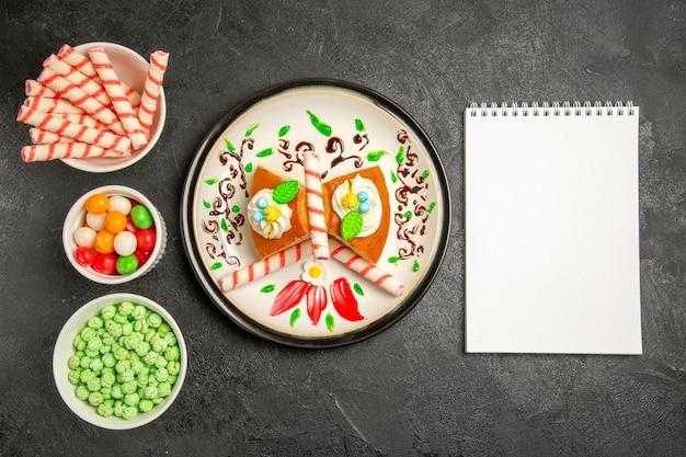 Draufsicht köstliche sahnetorte im inneren gestalteten teller mit süßigkeiten auf dunklem hintergrund kuchen süßer keks sahnetorte cookie