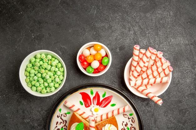 Draufsicht köstliche sahnetorte im inneren gestalteten teller mit süßigkeiten auf dunklem hintergrund kuchen süßer keks sahnetorte tee
