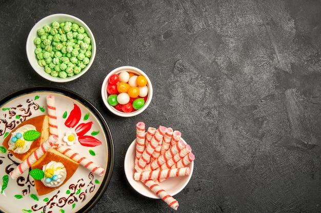 Draufsicht köstliche sahnetorte im inneren gestalteten teller mit süßigkeiten auf dunklem hintergrund süßer keks sahnetorte kuchen