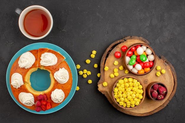 Draufsicht köstliche sahnetorte mit bonbons und tasse tee auf dunklem hintergrund kandiszuckerkuchen-keks-teig-frucht