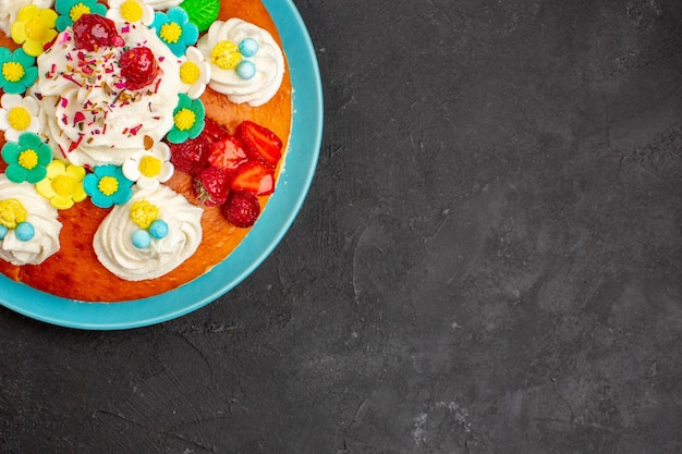 Draufsicht köstliche sahnetorte mit früchten auf dunklem hintergrund kuchenplätzchen süßer kuchenteekeks