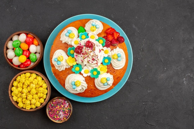 Draufsicht köstliche sahnetorte mit früchten und süßigkeiten auf dem dunklen hintergrund tortenkeks süßer tee-keks-kuchen